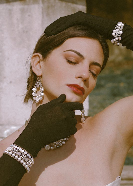 A beautiful women with black long gloves in an Italian garden wears stunning Ziio Jewels made of pearls, mother of pearls form the collection called Shinju. Shinju means Pearl in Japanese